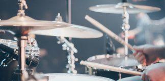 Person spiller trommer med lys ovenfra