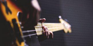 person spiller på brun bas i et mørkt rum