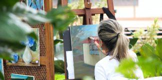 dame maler et maleri udenfor i sin have